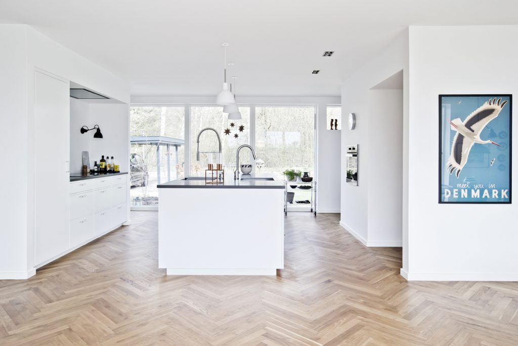 1960'er typehus fik facelift, Køkkenet har direkte adgang til øst- og vestvendte terrasser. De store glaspartier lukker masser af lys ind i det store rum.