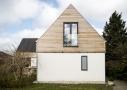 Facaden er filtset med indfarvet hvid puds, gråsorte vinduer og døre i træ/alu og cedertræ i gavl.