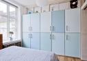Harmonisk farveskala på skabslågerne i soveværelset. Det nye forældresoveværelse imødekommer familiens forkærlighed for naturligt lys. Glaspartierne åbner op ind til lejlighedens spiseplads og skabslågernes blå farveskala skaber en rolig og harmonisk stemning.