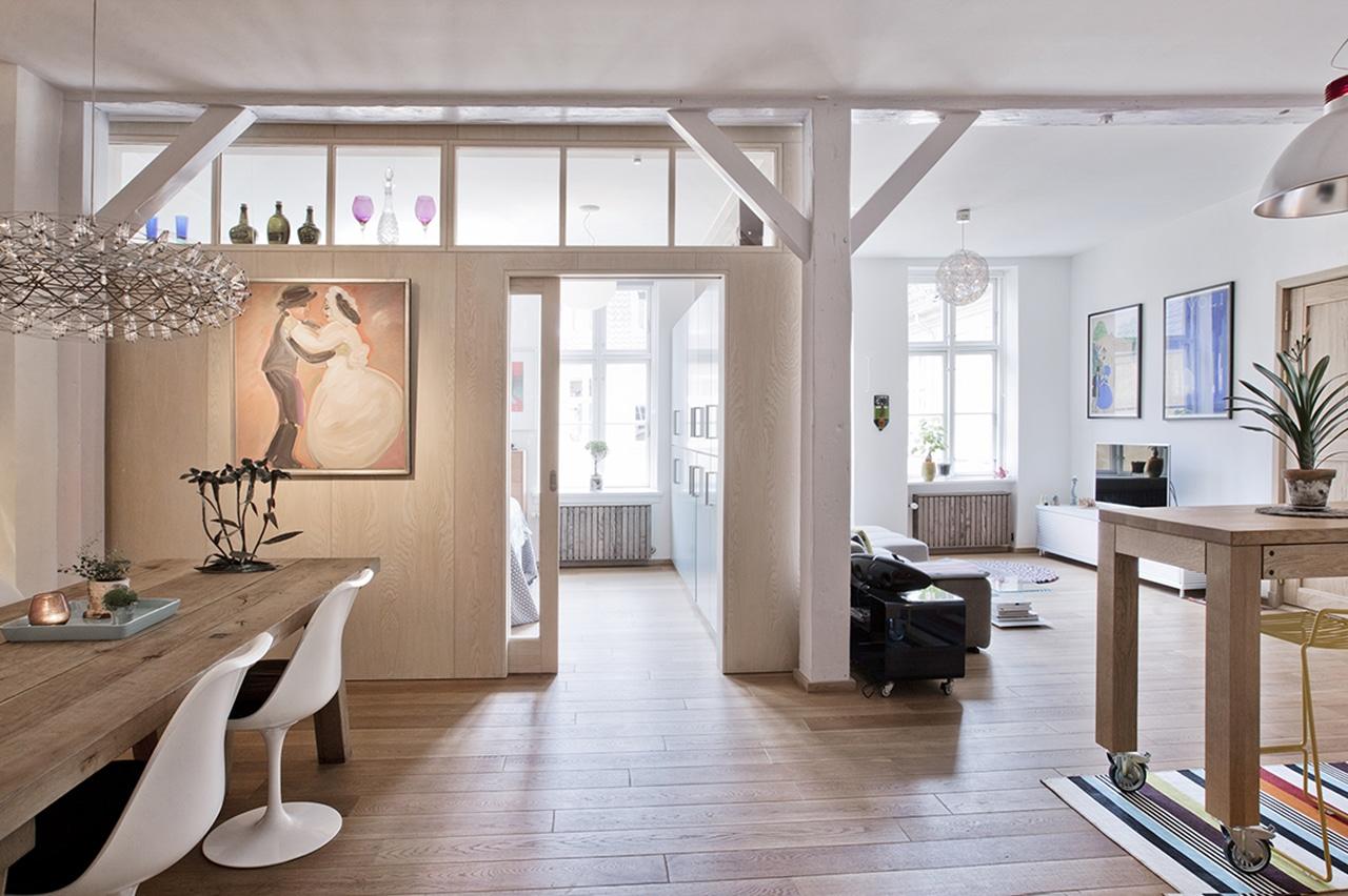 Dagslyset gennem soveværelse og stue. Ved at fjerne en længe af køkkenet er der blevet åbnet op til resten af lejligheden og skabt sammenhæng mellem boligens rum. Det mobile arbejdsbord bliver alrummets naturlige centrum, hvorfra man har overblik over stuen og spisepladsen.
