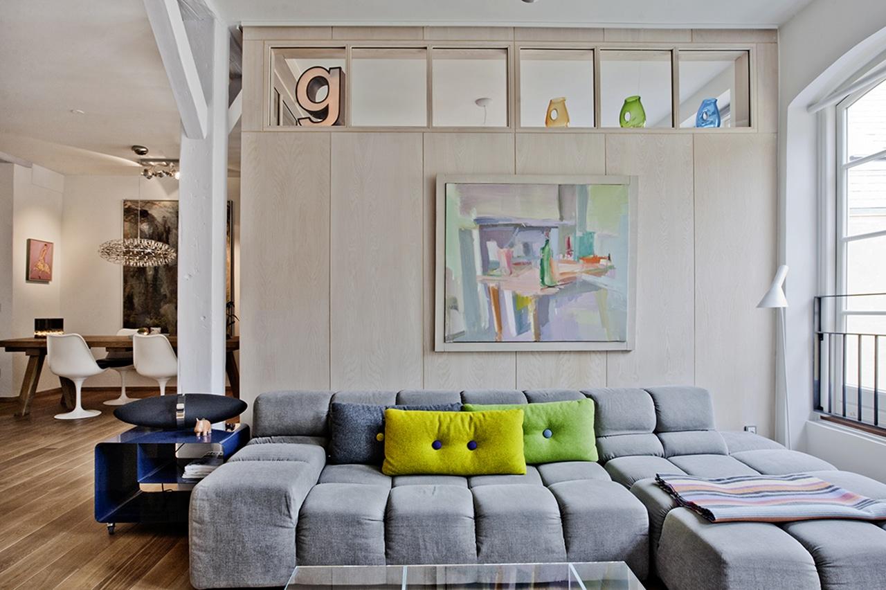 Træbeklædte vægge holdes fri af de markante tømmerkonstruktioner. Lejlighedens dybde gjorde det til en udfordring at få dagslys ind de bagerste rum. Ved at sætte et glasparti ind mellem spiseplads og soveværelse, trænger dagslyset helt ind til de bagvedliggende rum.