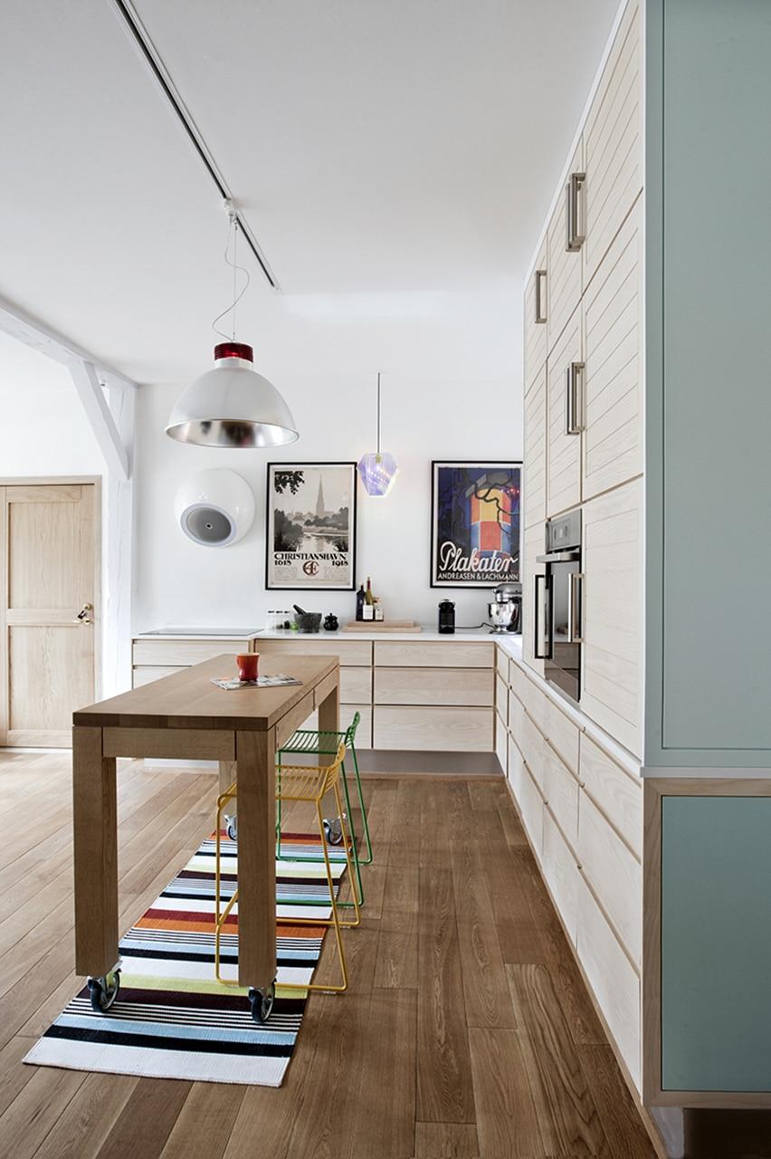 Snedkerkøkkenet er udført af Claes Amtorp. Køkkenet i lyst asketræ er snedkereret specielt til familien og spiller smukt sammen med det mørke egetræsgulv.