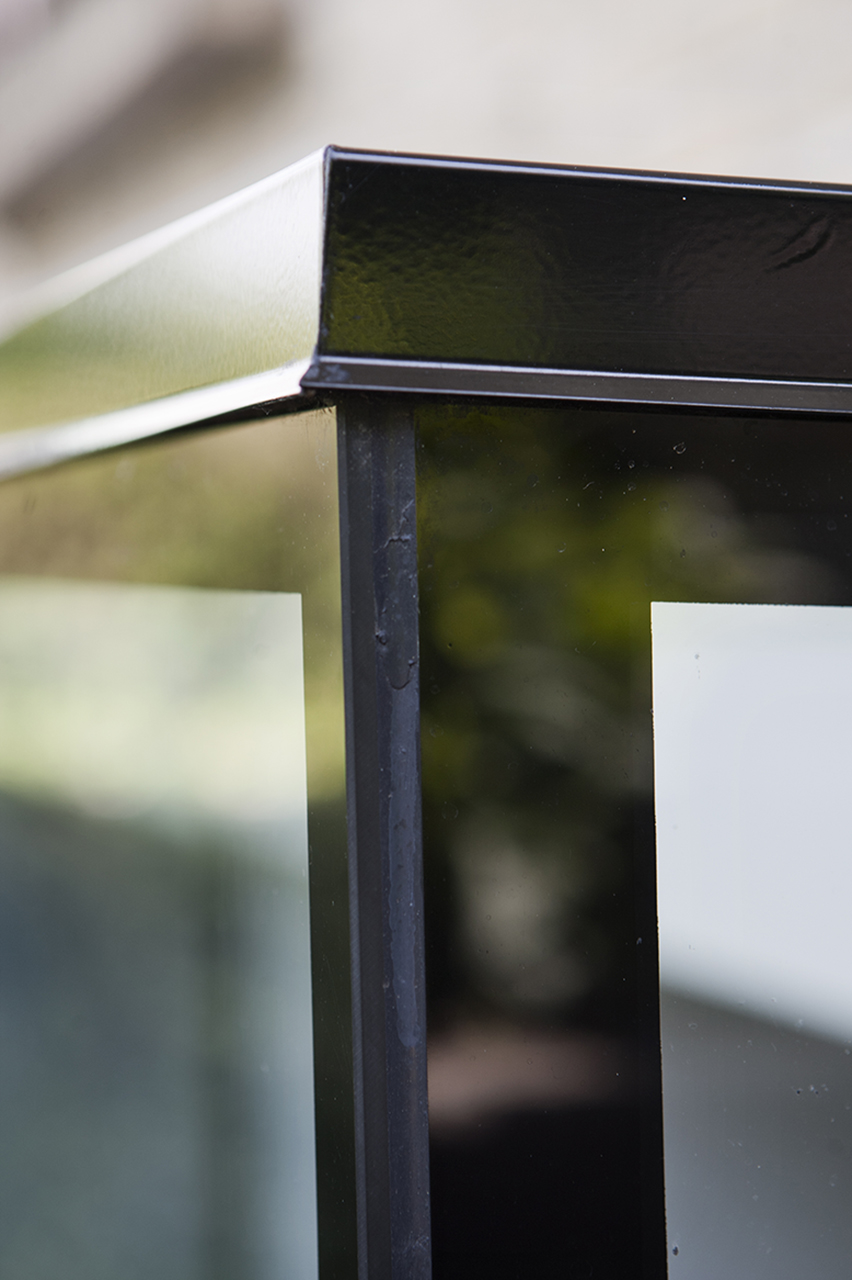 """De sorte """"bånd"""" på glaskonstruktionen er silkemaling på bagsiden af glasset, som skjuler de limede samlinger."""
