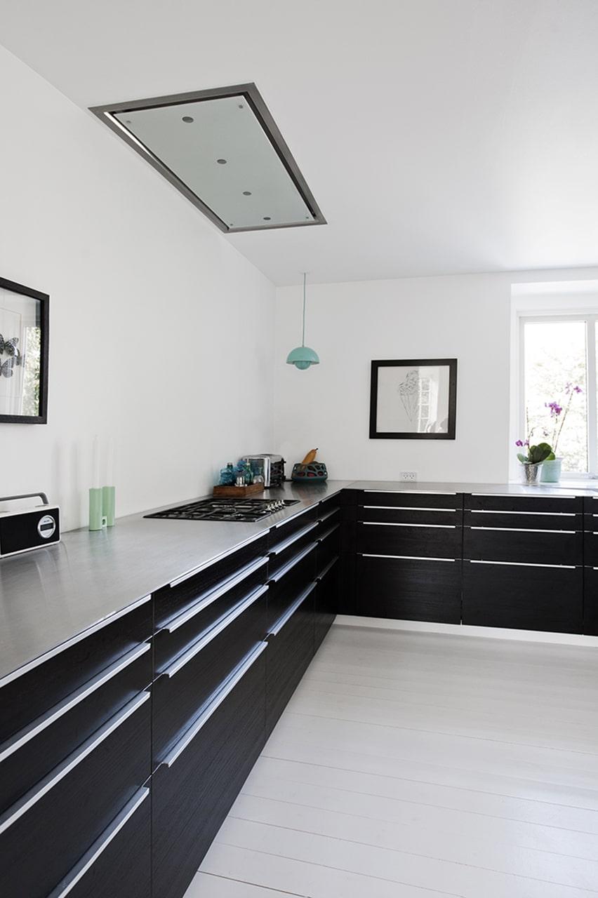 Køkkenbordplade i massivt rustfrit stål og isvejst gasblus samt køkkenvask.