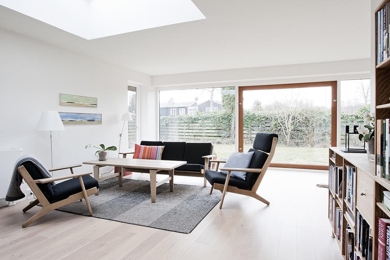 Stue EFTER ombygning. Stuen har fået optimeret dagslysforholdene ved etablering af ovenlysvinduer og det store glasparti, der giver udsyn til haven.
