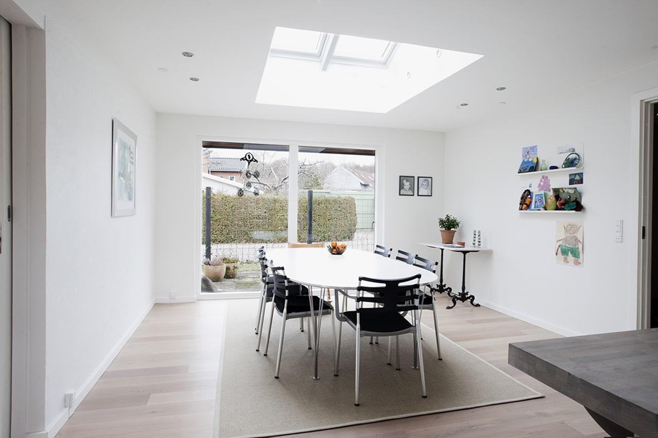 Ved spisepladsen i køkkenet er der etableret ovenlys, som giver et fantastisk lysindfald året rundt. I facaden giver en skydedør udgang til en lille vestvendt terrasse.