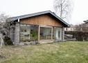 Havefacade efter ombygning. Fra stuen blev der åbnet op mod haven via et glasparti med skydedør. Gavlbeklædningen er skiftet til en lodret træbeklædning af cedertræ.