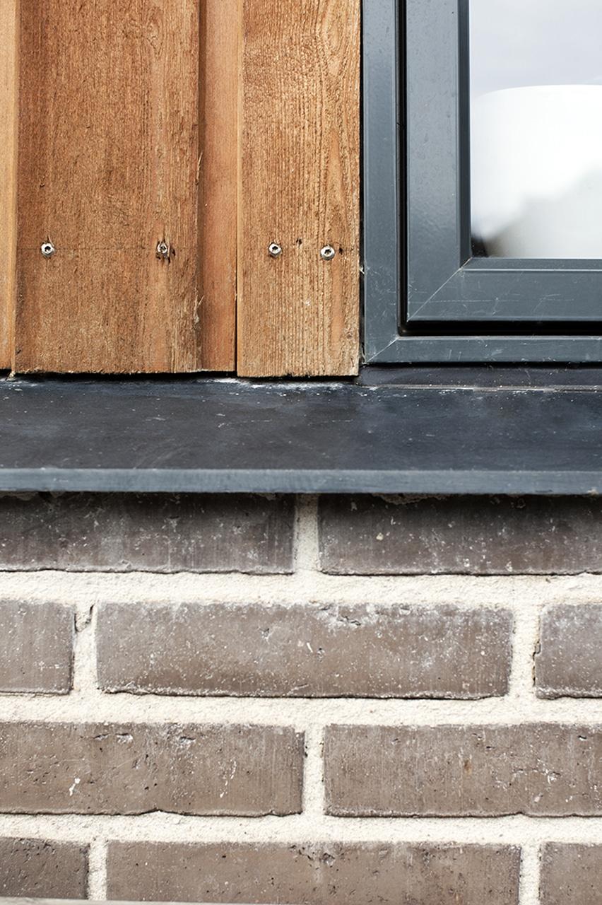 Facadedetalje og dagslys. Materialevalget i facaden er en komposition af de oprindelige brunlige facadesten, sålbænke i sort skifer, antracitgrå vinduer og døre og lodret cedertræsbeklædning.