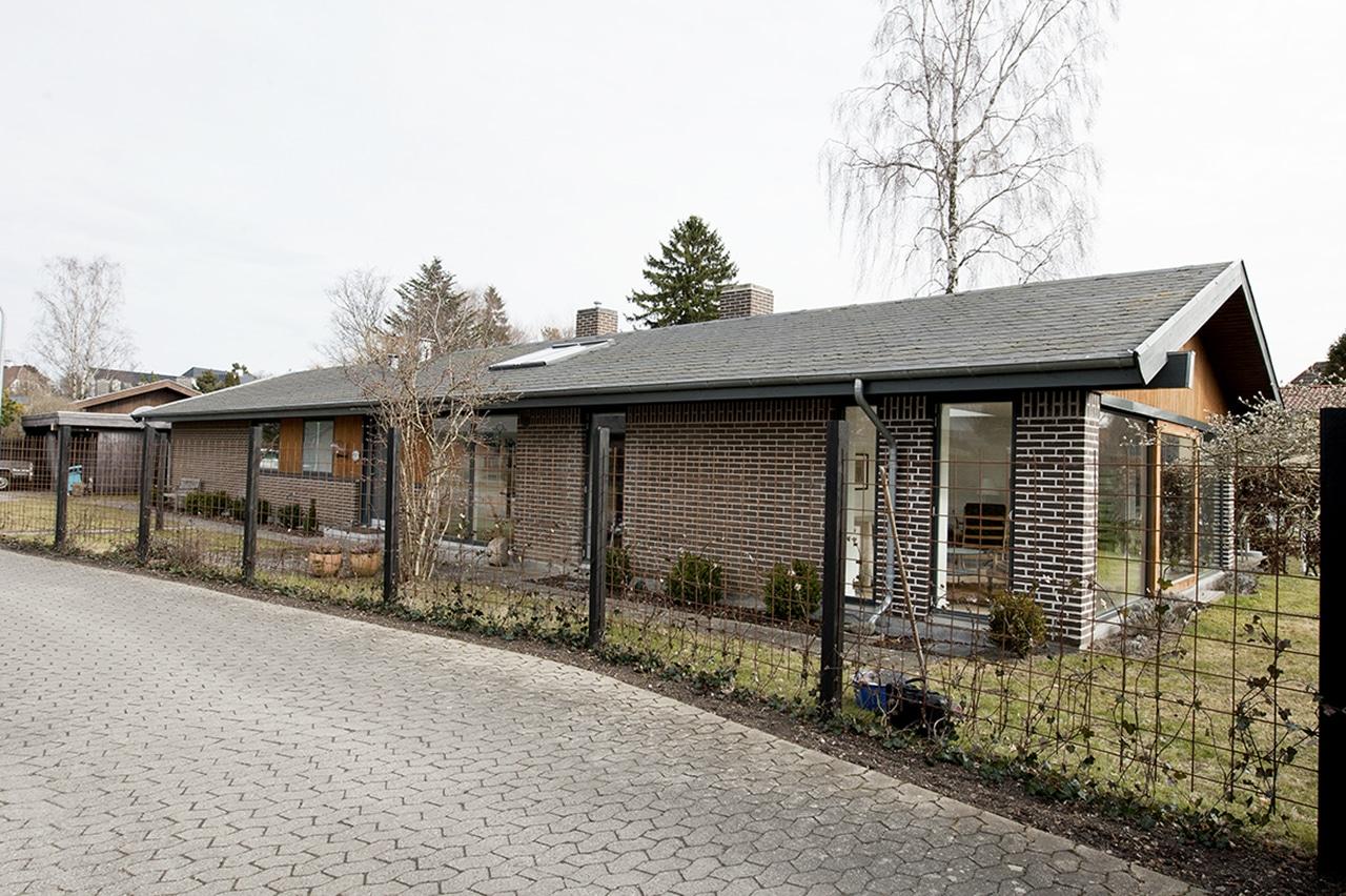 Facade mod vej. Den langstrakte facade har med vinduespartier fra gulv til loft givet mere dagslys i huset og en vekslende facaderytme.