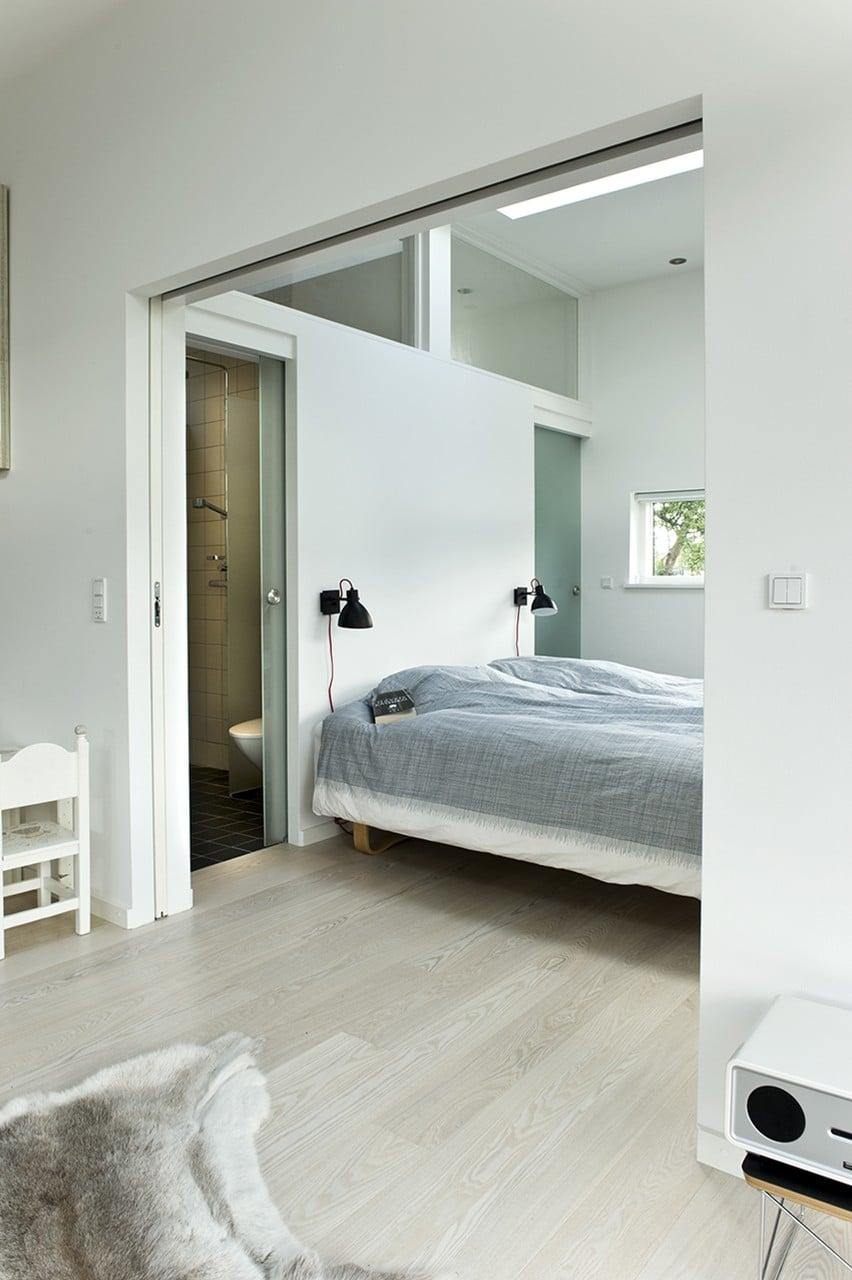Soveværelse med skydedør og udsigt til haven.