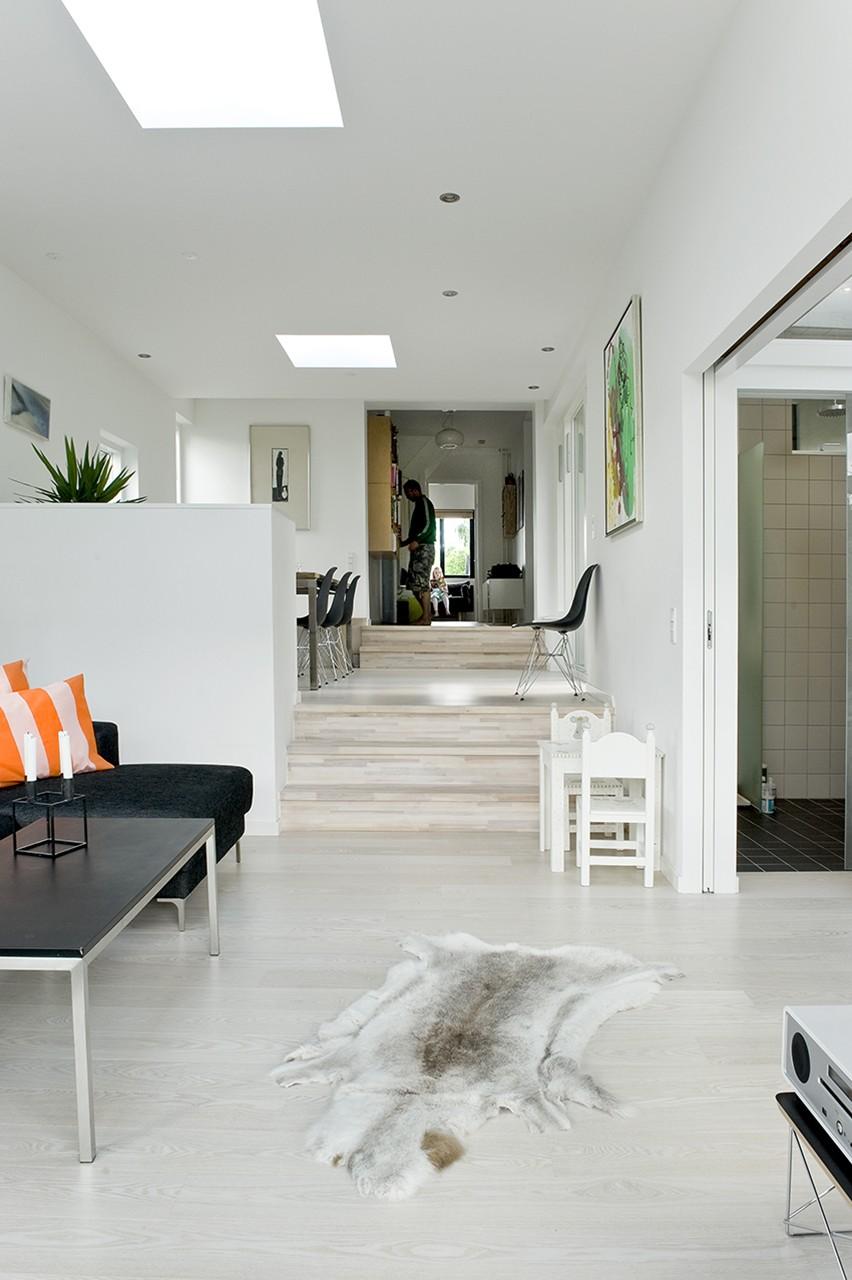 Opholdsrum i to niveauer. Tilbygningen er bygget i to niveauer. Det øverste niveau er indrettet med spisestue og har udgang til en sydvendt terrasse. Det nederste niveau indeholder stue med plads til hele familien samt forældresoveværelse. Begge rum har udgang til en vestvendt terrasse.