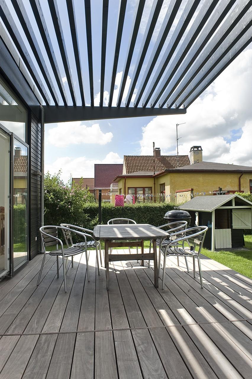 Halvtag med lameller. Lamellerne i det karakteristiske halvtag skærmer for solen og gør, at man kan bruge terrassen for enden af tilbygningen på selv de varmeste sommerdage.