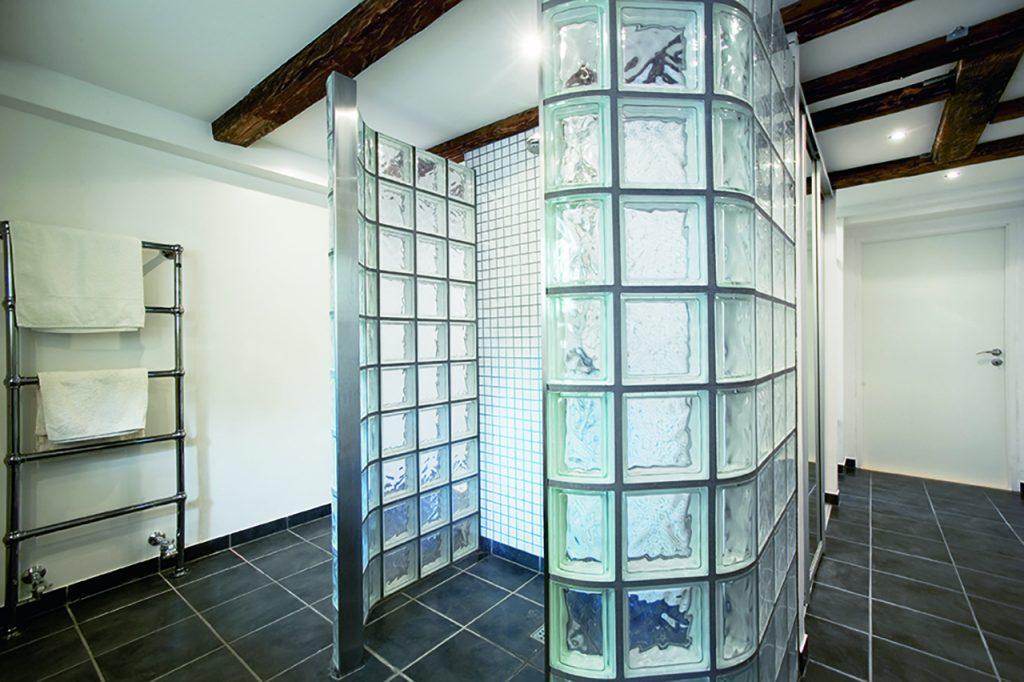 """Ny kælder med lækkert luksusbad og """"Klargøringshal"""" til hele familien. Brusebad tages bag glasbyggestenene. I de øvrige funktionsnicher er der kar, toilet og garderobeskab."""
