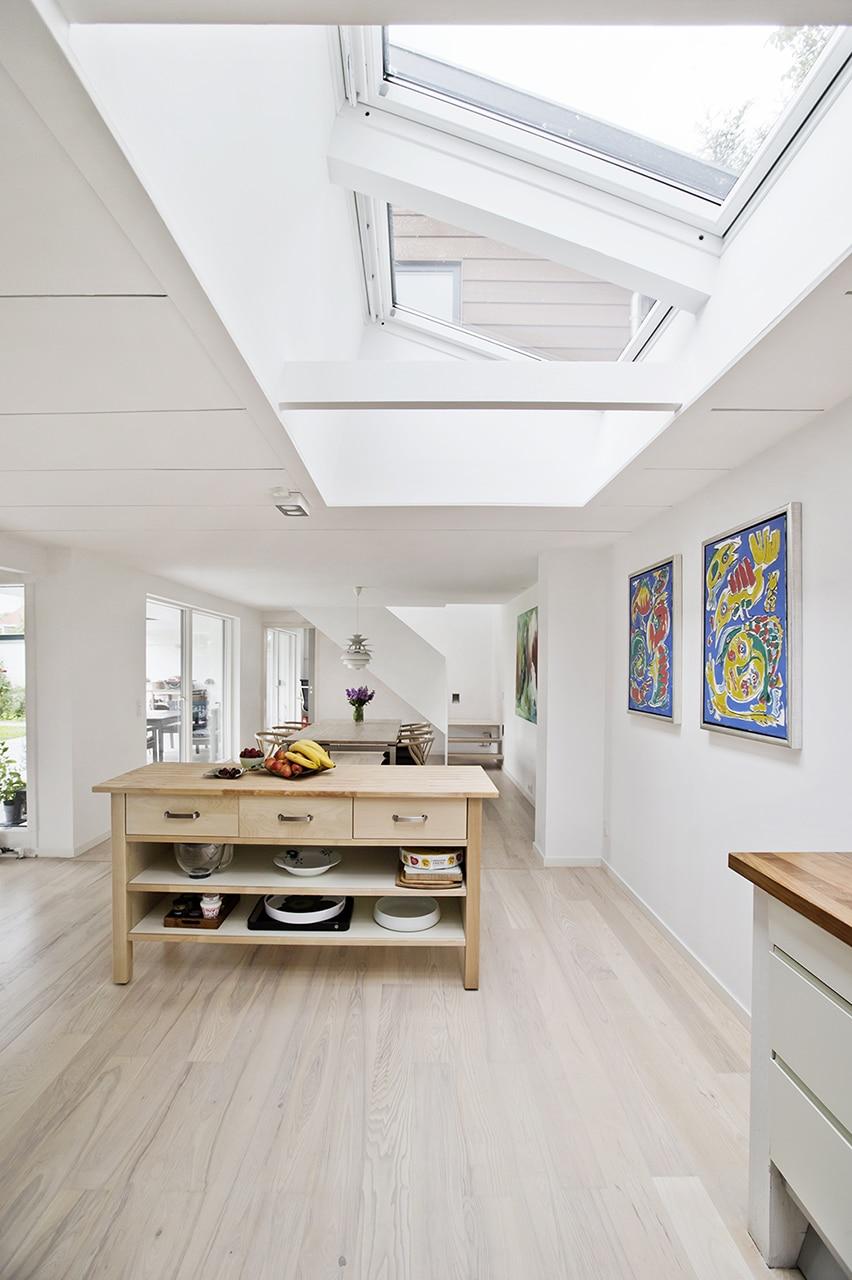 Parcelhus fik to etager og haven helt ind i stuen, og trækker dagslys ind i køkken med store ovenlysvinduer.