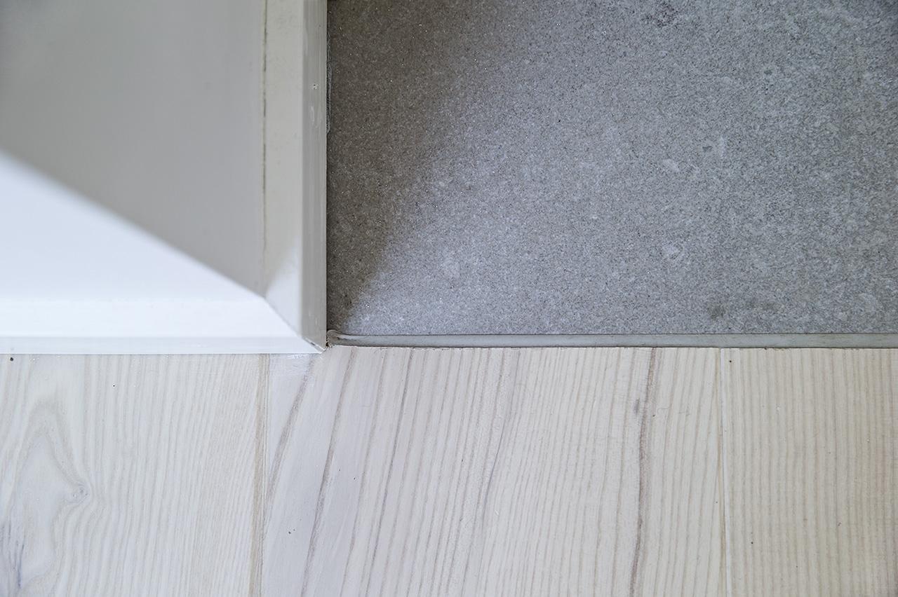 Detaljeovergang mellem sten og trægulv Det kræver en dygtig entreprenør, at lave en detaljeovergang mellem sten og trægulv, med en indfarvet elastisk fuge, i stedet for en metalliste.