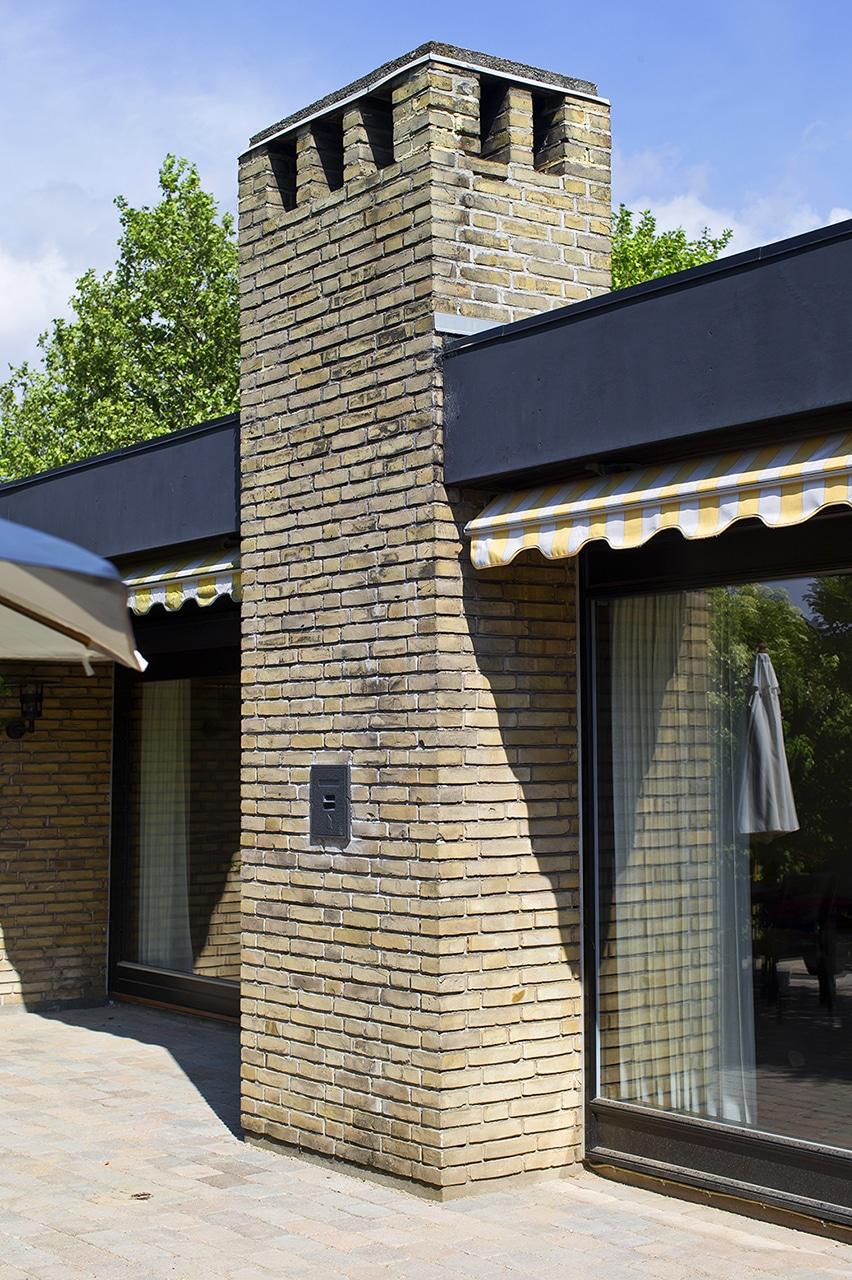 De sorte vinduespartier støder flot op mod den murede skorsten.