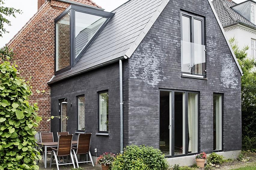 Klassisk murermestervilla fik nyt liv. Tilbygningen er pudset op med sort indfarvet puds med et dertil matchende mørkt tag.
