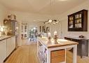 Køkken med snitte/hakkeø og vitrineskabe. Køkkenet med både høje og lave siddepladser. Den brede åbning mellem rummene skaber mulighed for opdækning til mange gæster.