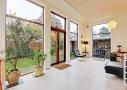 Fra den højloftede stue er der frit udsyn til den smukke have. Loftet er listebeklædt, hvilket skaber en god akustik i rummet.
