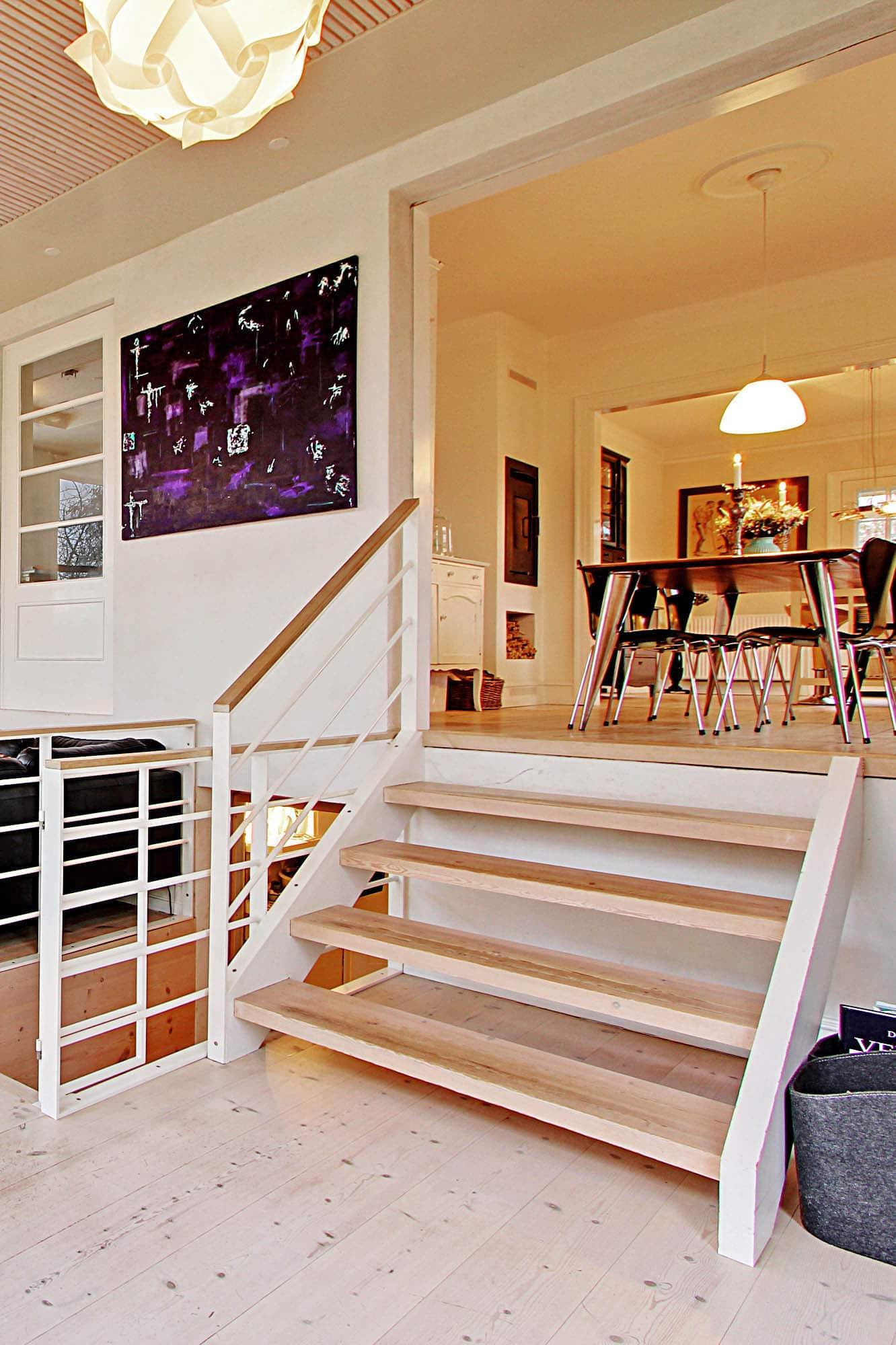 Trætilbygning med højt til loftet og kig til havens frugttræer og niveauskift til køkken-alrum.