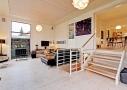Højloftet stue i tilbygning. Fra den nye stue er der adgang til både det højere liggende køkken alrum og kælderen.