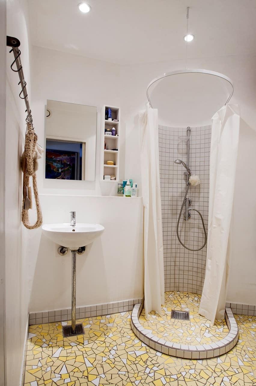 Kakkelovnsniche anvendes nu som bruseniche. Badeværelset er placeret i midten af lejligheden uden direkte dagslys. Gulvmønstret med de knækkede fliser er ikke en standardvare, men derimod et resultat af bygherres møjsommelige arbejde, udført efter skabeloner på A3 størrelse.