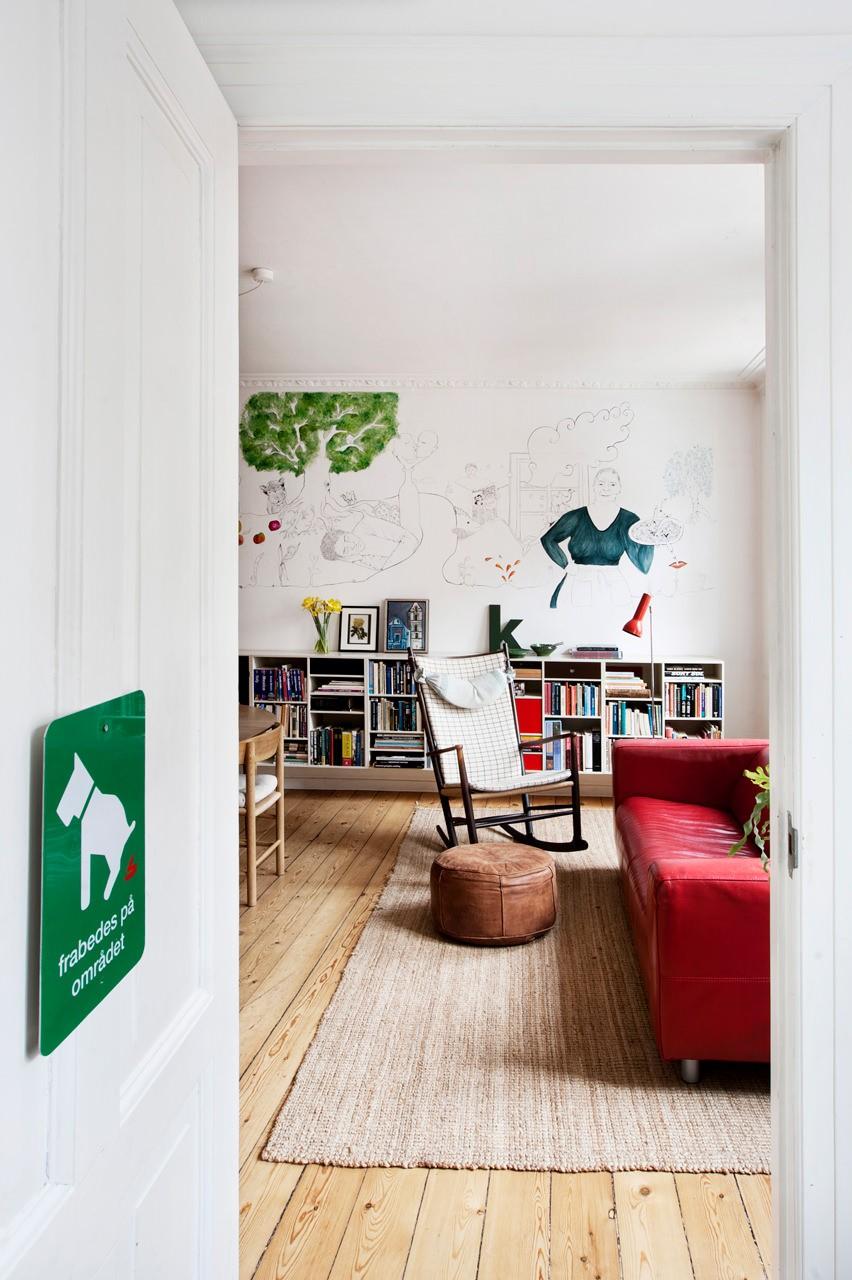 Brug dagslys via et højtsiddende vindue i køkkenet. Køkkenapteringen er meget minimalistisk og kokken kan betjene alle funktioner uden at vandre rundt. Til højre ses et kig fra det ene værelse til alrummet.