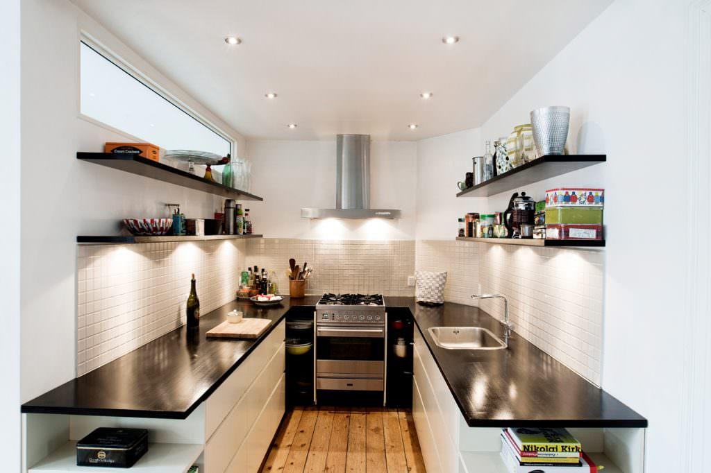 Ombygning fra 3 til 5 værelses lejlighed. Brug dagslys via et højtsiddende vindue i køkkenet. Køkkenapteringen er meget minimalistisk og kokken kan betjene alle funktioner uden at vandre rundt. Til højre ses et kig fra det ene værelse til alrummet.