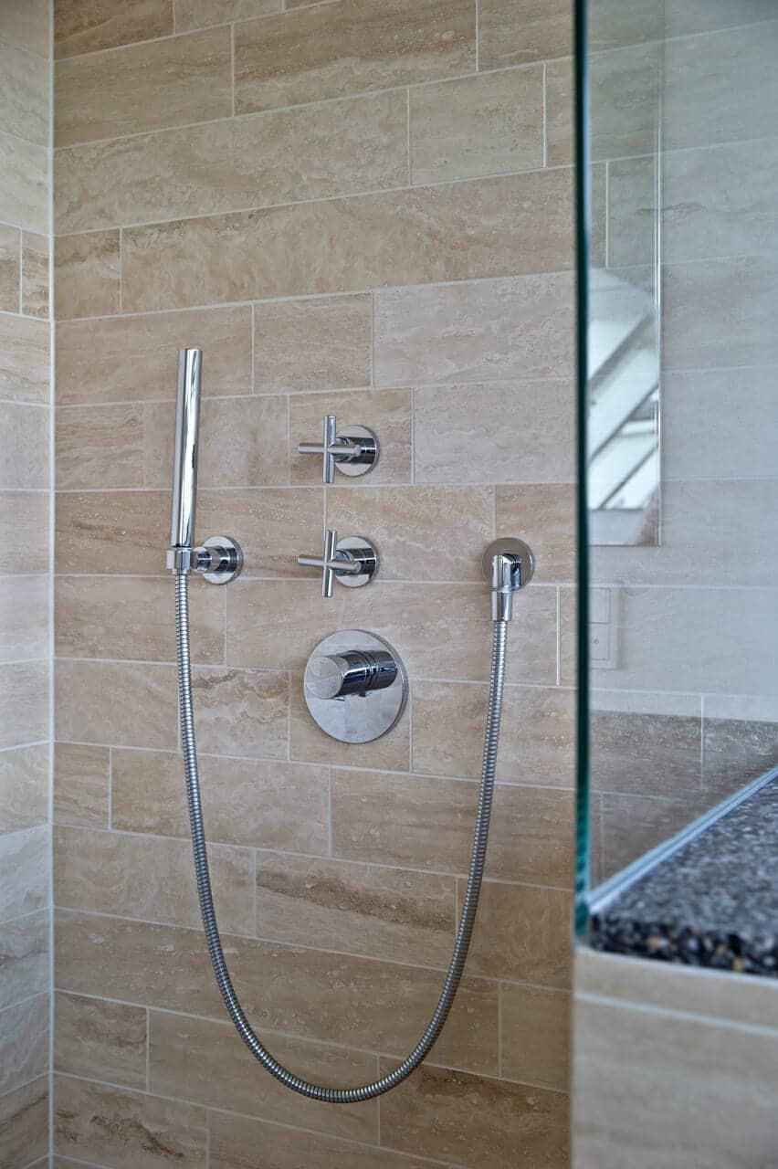 Den nye brusekabine er lavet i hærdet glas, som giver et fint modspil til de rustikke gulve.