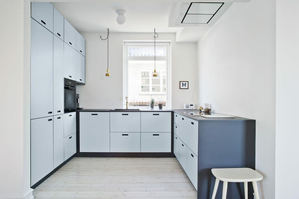 Nyt køkken og bad i murermestervilla fra 1920erne med stilrene lyseblå skabslåger og armatur i messing