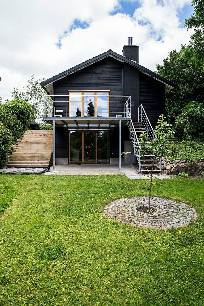 Sort træbeklædning har forvandlet det gule murstenshus fra 1960'erne fuldstændigt.