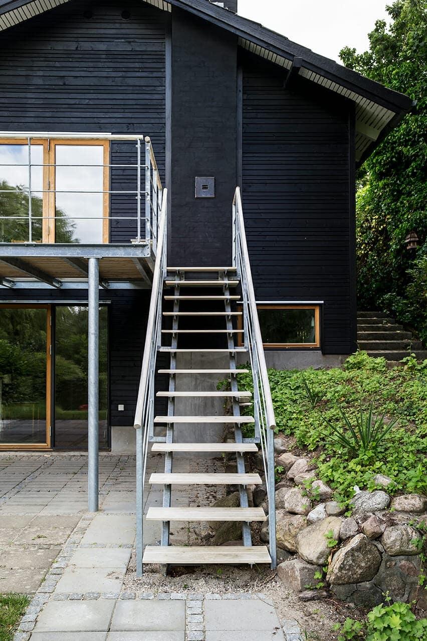 Trappe med let udtryk i træ og metal leder op til husets altan.