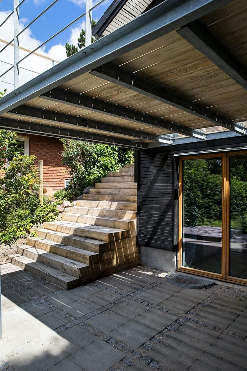 Ny flisebelægning på den overdækkede terrasse ud for kælder.