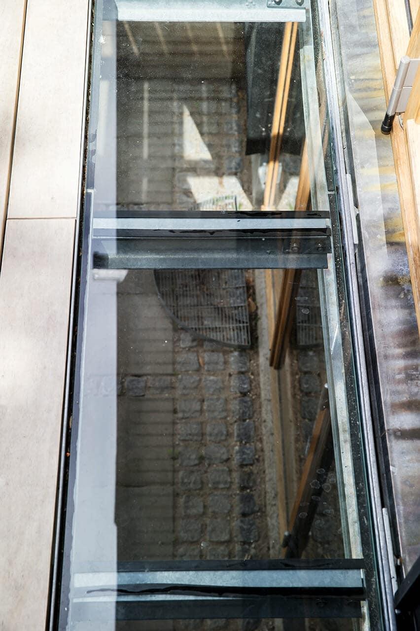 Glaspartier i gulvet på den nye altan leder dagslys nedenunder til den overdækkede terrasse.