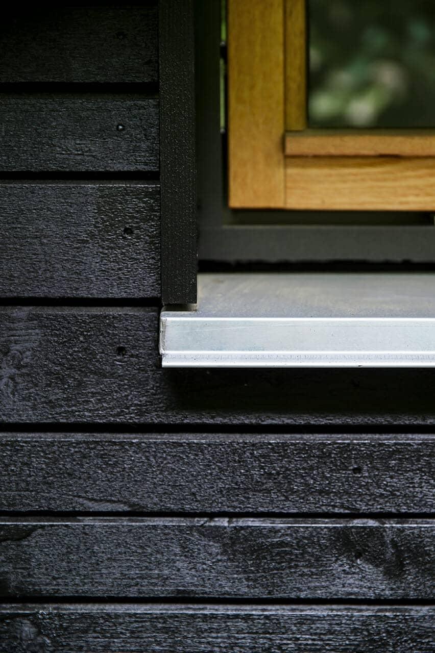 Ny sort træbeklædning i varierende bredder giver lysspil i facaden