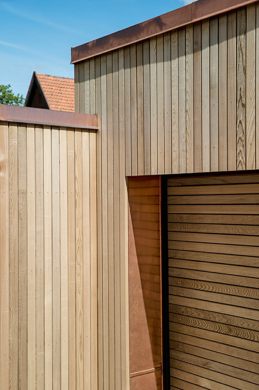 Garage og skur med lodret og vandret listebeklædning i cedertræ samt kobberinddækninger