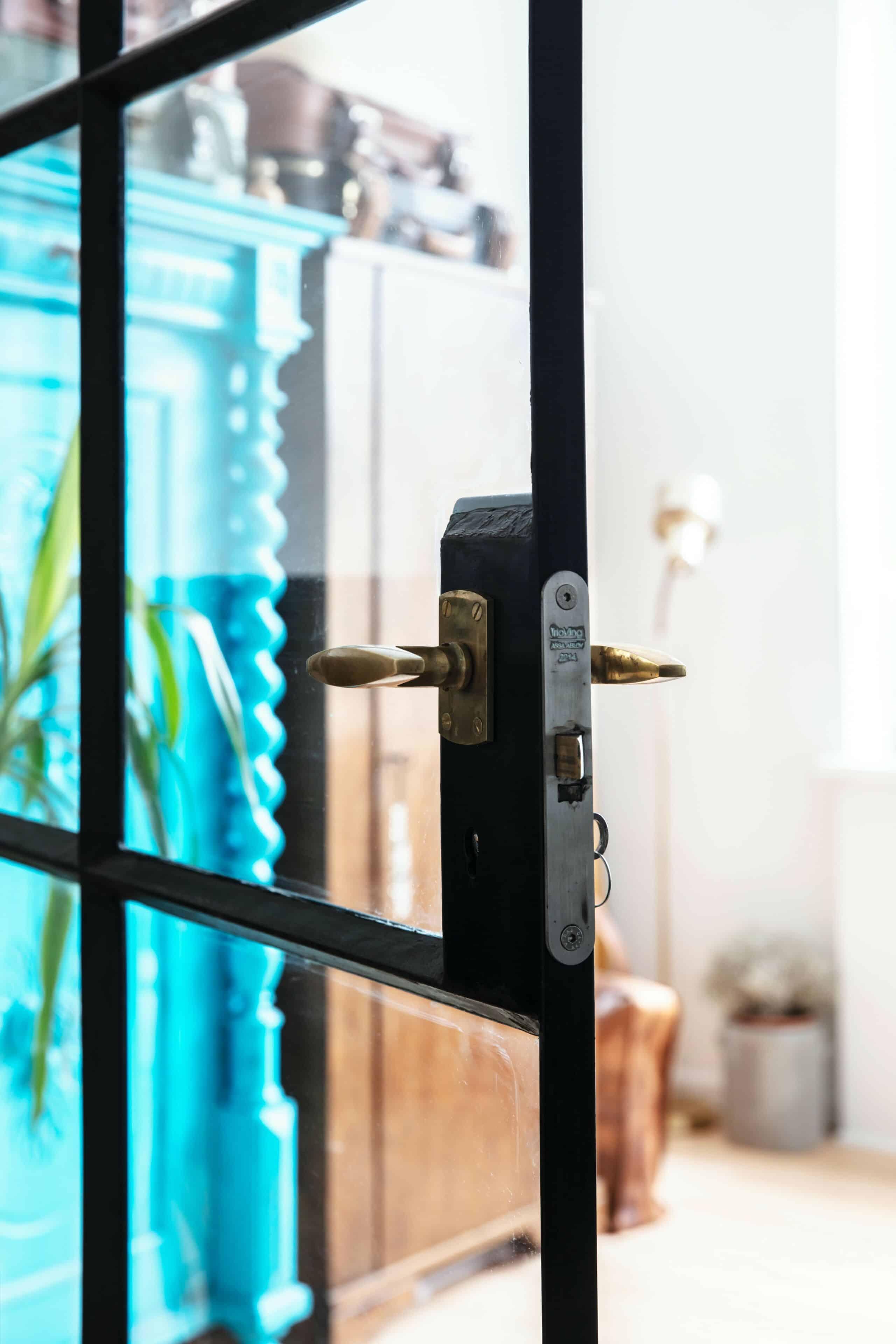 Glasvæg med smedejernsgitter og originale dørhåndtag bevaret i arkitekttegnet ombygning af funkislejlighed
