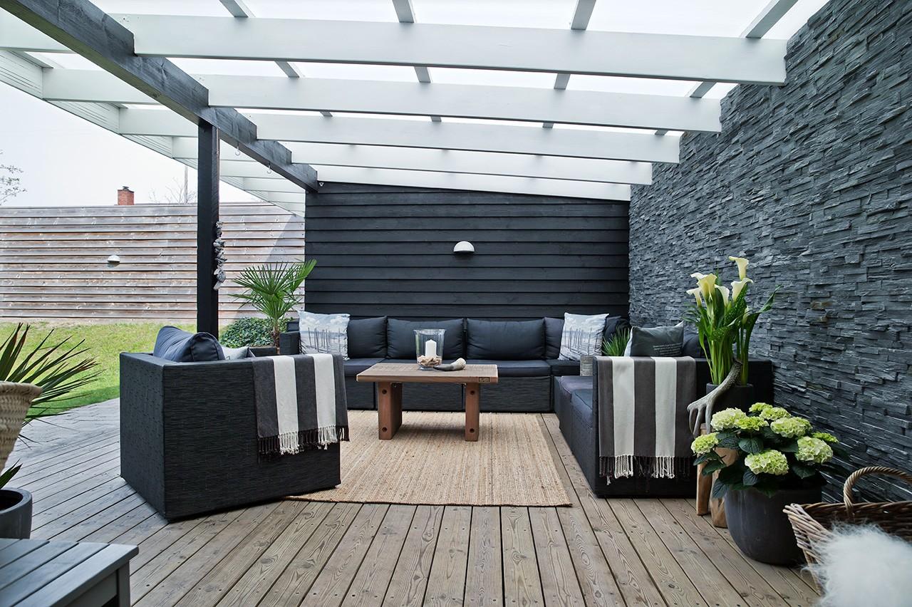 Terrasse med lys overdækning og grå skifervæg