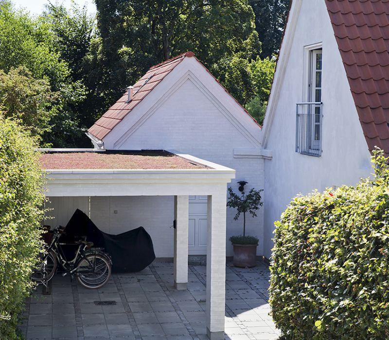 Carporttaget er en mos-sedum tagbeplantning. Annekset er rykket væk fra hovedhuset og danner med den nye carport et hyggeligt gårdrum, som byder en velkommen.
