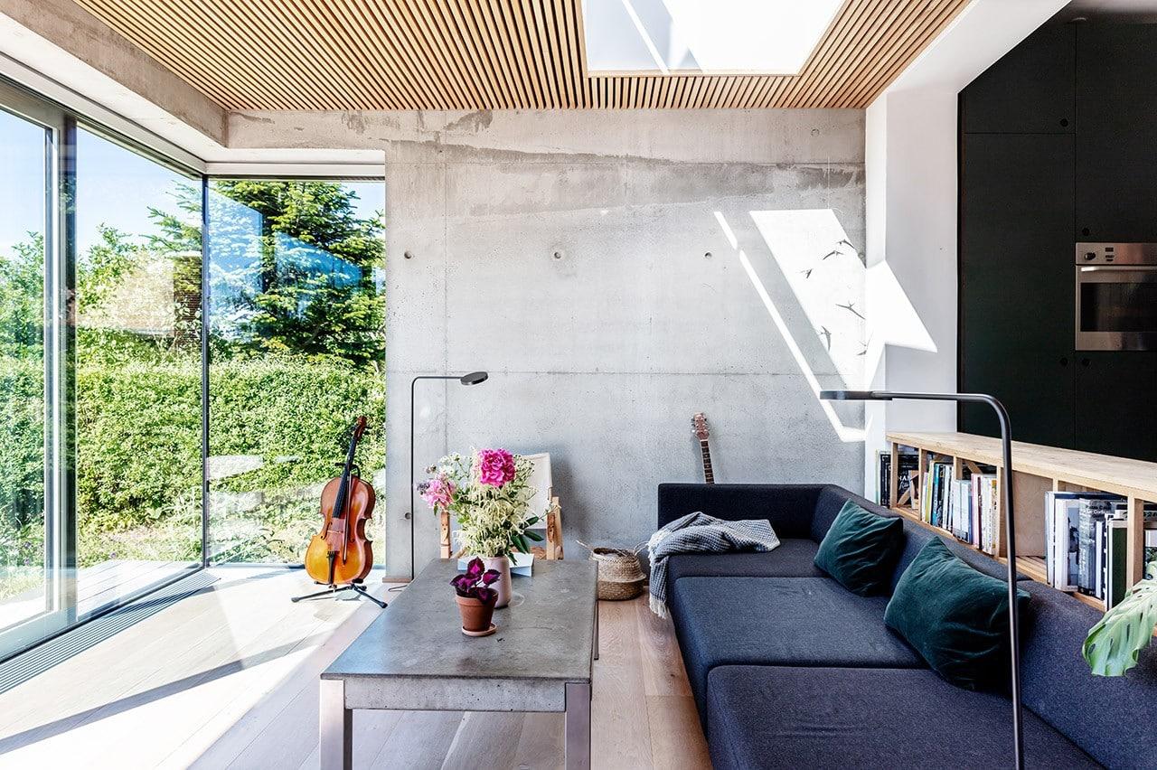 Sofa med udsigt til haven gennem kæmpe panoramavinduer