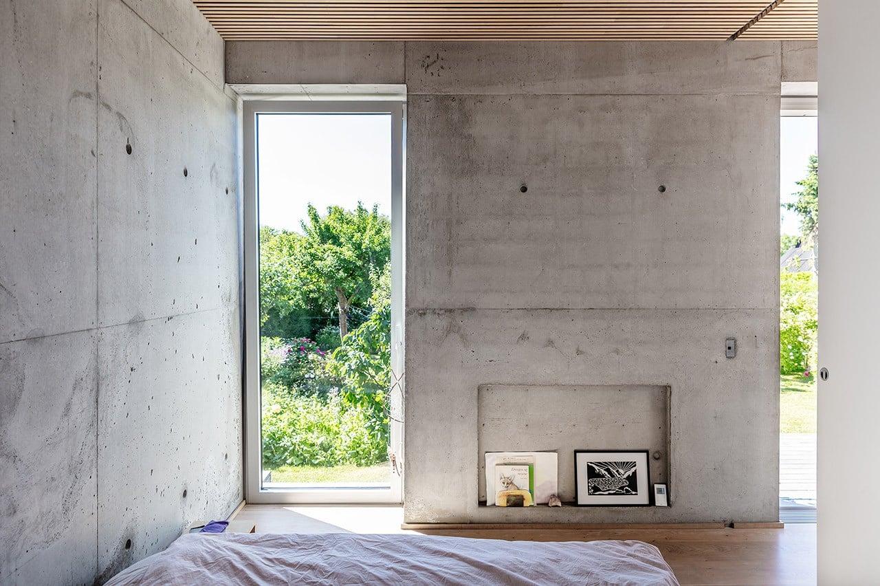 Soveværelse med zen-stemning, rå betonvægge og fantastisk udsigt til haven