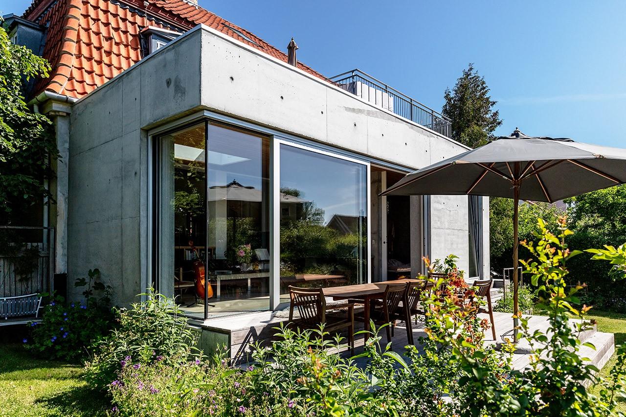Ny tilbygning med søjleløst hjørne i kontrast til murermestervilla fra 1920'erne